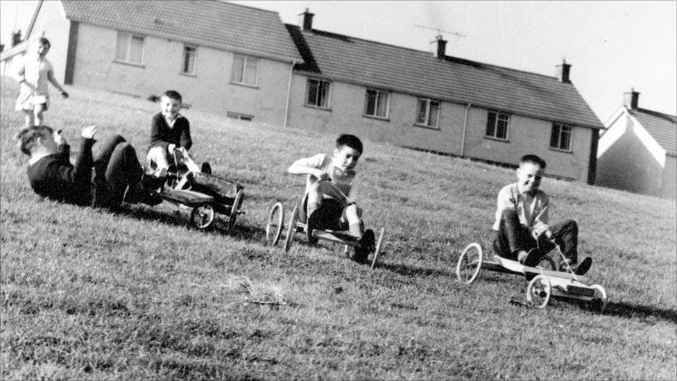 Young boys racing down a grass hill on go-carts